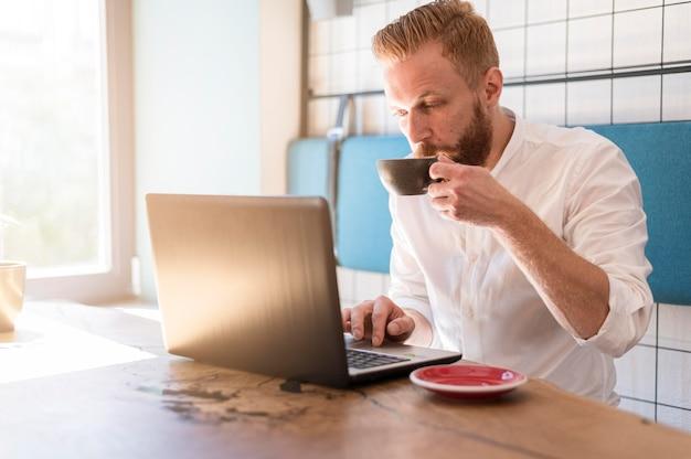 Moderner mann, der an seinem laptop beim kaffeetrinken arbeitet