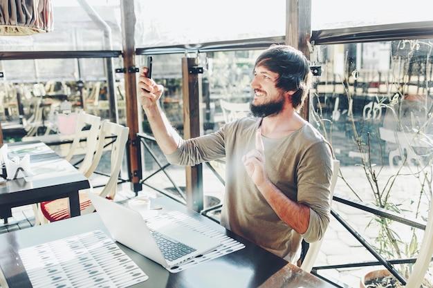 Moderner mann, der ein selbstporträt mit seiner digitalkamera für smartphones schafft, schaffend, wenn er in einem sozialen netz fotografiert