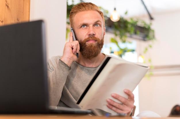 Moderner mann, der einen anruf macht, während er sein notizbuch hält