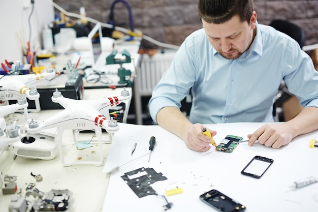 Moderner mann, der im elektronik-service-shop arbeitet