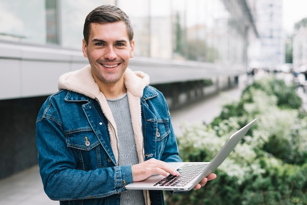 Moderner mann, der laptop in der städtischen umwelt verwendet