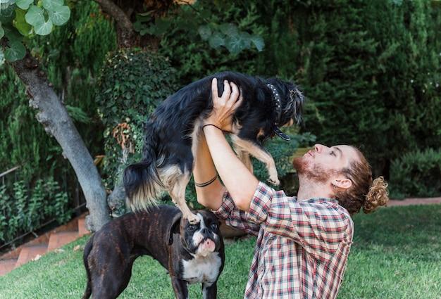 Moderner mann, der mit hunden im garten spielt
