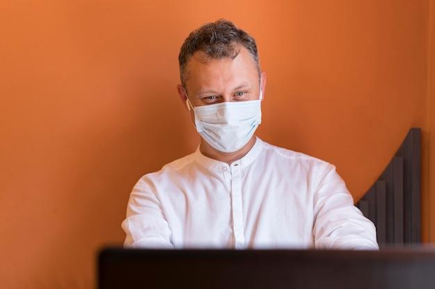 Moderner mann, der mit seiner medizinischen maske arbeitet