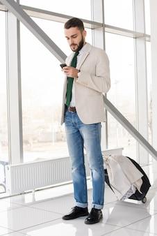 Moderner mann, der nachrichten im flughafen überprüft