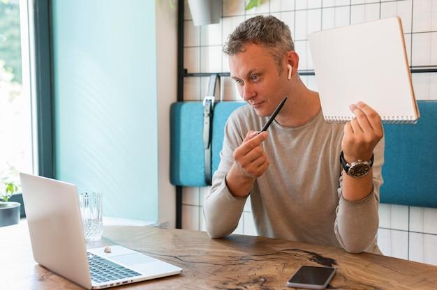Moderner mann, der notizen auf videoanruf zeigt