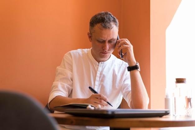 Moderner mann, der notizen in seinem büro macht