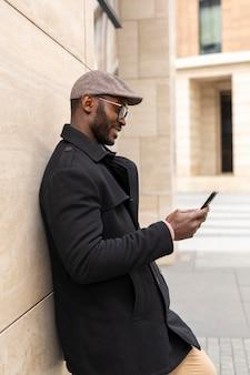 Moderner mann, der sein telefon im freien benutzt