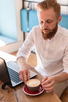 Moderner mann, der seine tasse kaffee neben seinen laptop stellt