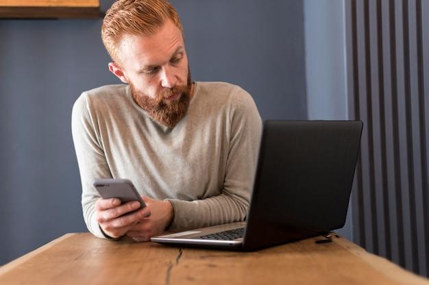 Moderner mann, der seinen laptop betrachtet