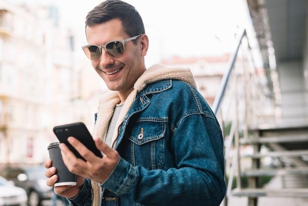 Moderner mann, der smartphone in der stadt verwendet