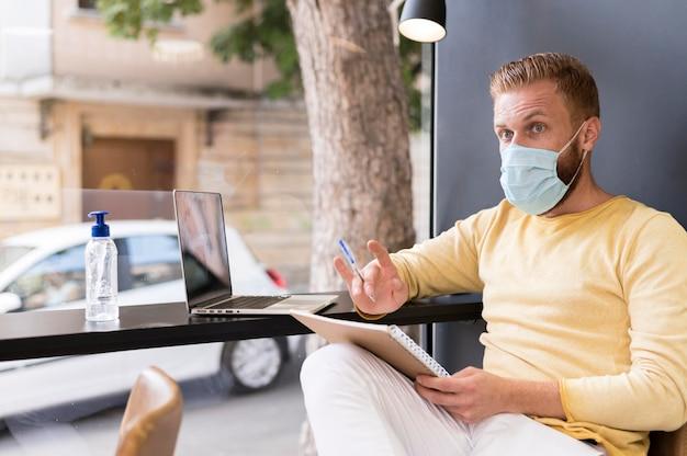 Moderner mann, der unter verwendung der medizinischen maske arbeitet