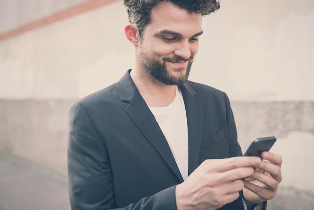 Moderner mann des hübschen hippies, der intelligentes telefon verwendet