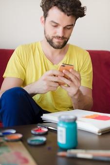 Moderner mann des hübschen hippies, der mobiltelefon verwendet