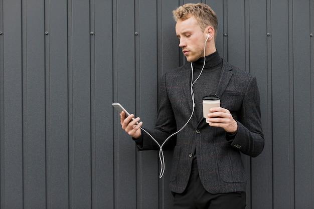 Moderner mann mit dem kaffee, der smartphone betrachtet