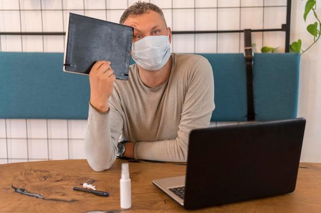 Moderner mann mit der medizinischen maske, die ein notizbuch hält