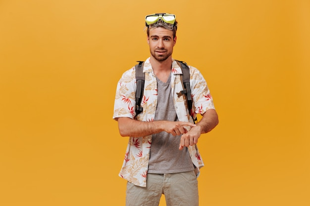 Moderner mann mit ingwerbart in hellgrüner schwimmbrille und sommerlicher cooler kleidung mit blick in die kamera an der orangefarbenen wand