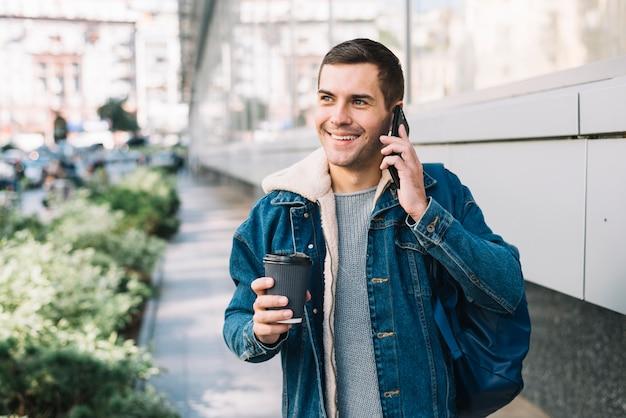 Moderner mann mit kaffeetasse in der städtischen umgebung