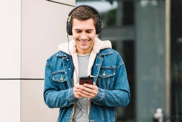 Moderner mann mit kopfhörern im städtischen umfeld