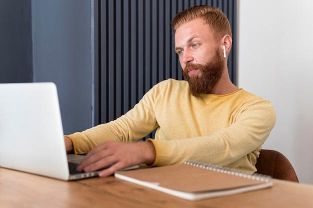Moderner mann mit ohrhörern, die zu hause arbeiten