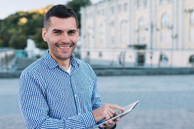 Moderner mann mit tablette in der städtischen umwelt