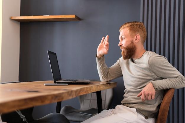 Moderner mann winkt, während er einen videoanruf hat