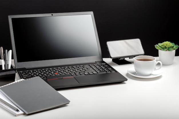Moderner minimaler arbeitsplatz für den mann. home-office-laptop-bildschirm leerer bildschirmarbeitsplatz. desktop mit laptop-pc-smartphone, bürolieferanten, kaffeetasse-pflanzenblume. langes webbanner.