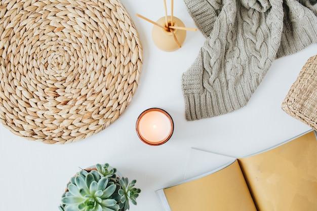 Moderner minimaler heimarbeitsplatz im boho-stil mit notizbuch, saftigem, gestricktem plaid, kerze, aromastäbchen, strohgeflechtservietten auf weiß
