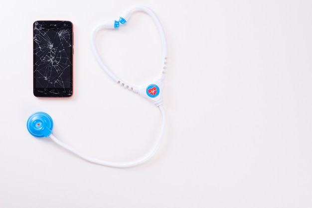 Moderner mobiler smartphone mit einem defekten schirm mit einem fanendoskop der kinder lokalisiert auf einem weißen hintergrund. von oben betrachten