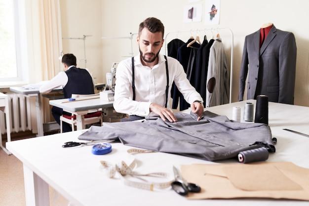 Moderner modedesigner, der im atelier arbeitet