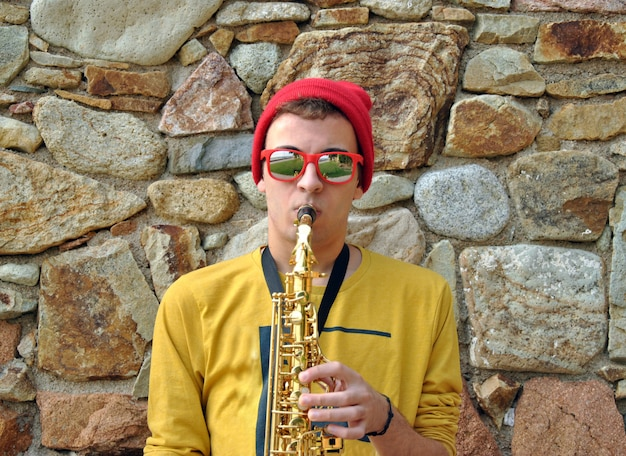 Moderner musiker, der mit seinem saxophon im garten aufwirft