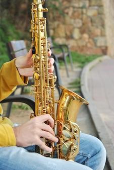 Moderner musiker, der mit seinem saxophon im strand aufwirft