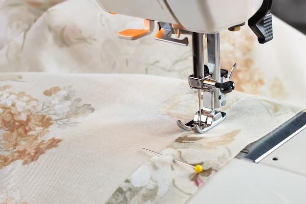 Moderner nähmaschinen-nähfuß macht eine naht auf colofrul-stoff. nähvorgang