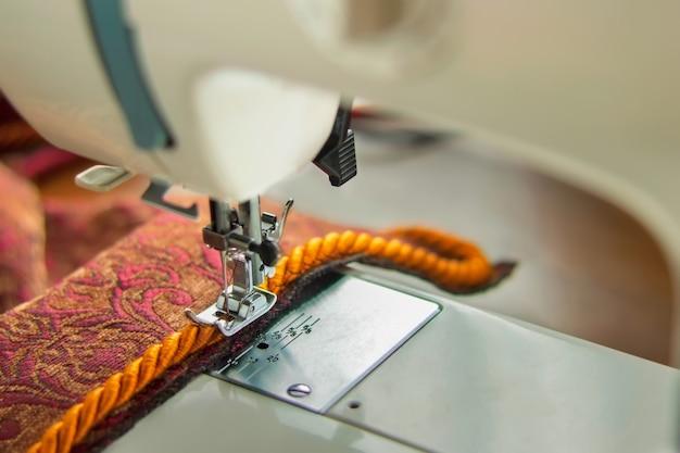Moderner nähmaschinen-nähfuß und dekorative kantenschnur. nähvorgang.