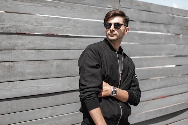 Moderner netter junger mann in einer modischen schwarzen jacke in der stilvollen sonnenbrille posiert im freien nahe einer hölzernen weinlesewand. attraktiver kerl, der an einem sonnigen sommertag auf der straße ruht.