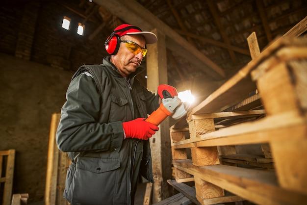 Moderner professioneller industriearbeiter in uniform mit schutz, der auf der holzpalette mit dem elektrischen schleifer arbeitet.