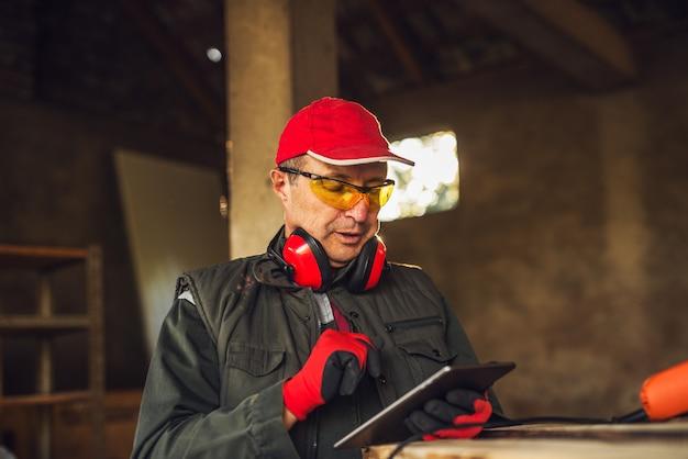 Moderner professioneller textilarbeiter mit schutz, der eine tablette hält und status der produktion prüft.