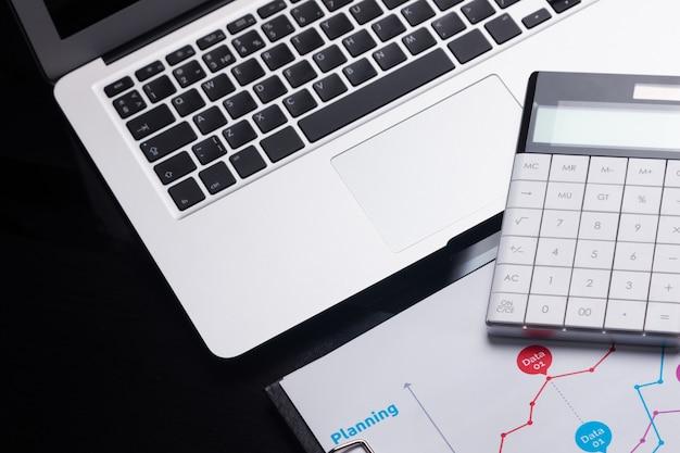 Moderner rechner ist auf einem laptop und auf einem blatt mit einem diagramm