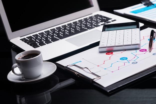 Moderner rechner ist das notizbuch und auf dem blatt mit dem stundenplan neben der kaffeetasse