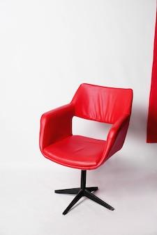 Moderner roter sessel auf weißem hintergrund im studio - vertikales foto