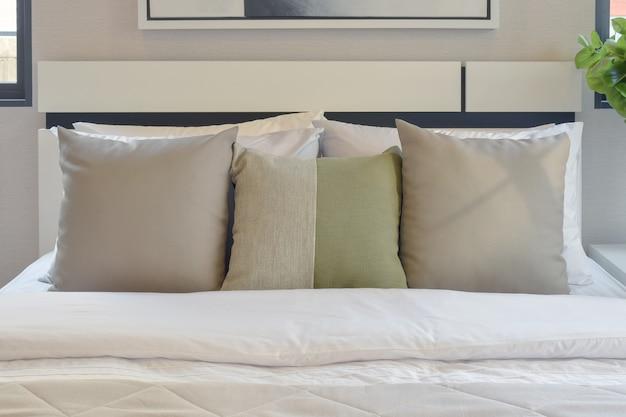 Moderner schlafzimmerinnenraum mit grünem und weißem kissen auf bett