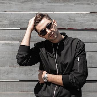 Moderner schöner junger mann in der trendigen schwarzen jacke in der stilvollen sonnenbrille mit einer frisur wirft nahe einer vintagen holzwand auf der straße auf. netter kerl entspannt sich an einem sommertag auf der straße. herrenbekleidung