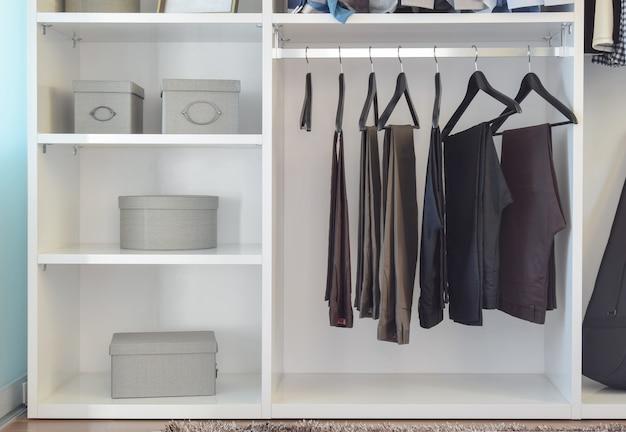 Moderner schrank mit hosenreihe, die in der weißen garderobe hängt