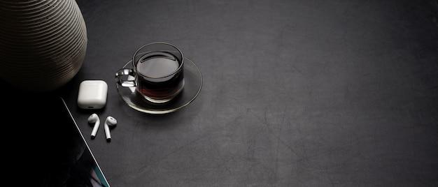 Moderner schreibtisch mit digitalem tablet, kaffeetasse, zubehör und kopierraum auf schwarzem ledertisch