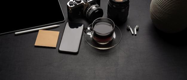 Moderner schreibtisch mit digitalem zubehör, kamera, kaffeetasse, notizblock und dekoration auf schwarzem ledertisch