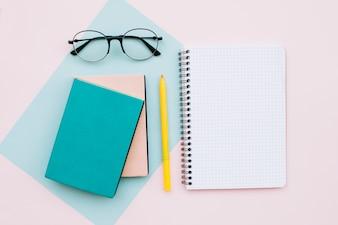 Moderner Schreibtisch mit Gläsern und Büchern und Notizbuch auf Pastellfarbhintergrund