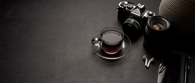 Moderner schreibtisch mit kaffeetasse, kamera, zubehör, dekoration und kopierraum auf schwarzem ledertisch