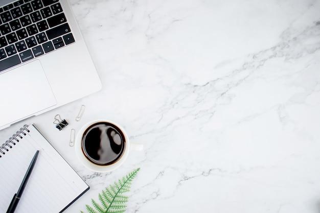 Moderner schreibtisch mit laptop-computer und americano-kaffee. draufsicht mit kopienraum, flache lage.