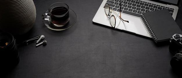 Moderner schreibtisch mit laptop, kaffeetasse, zubehör und kopierraum auf schwarzem ledertisch