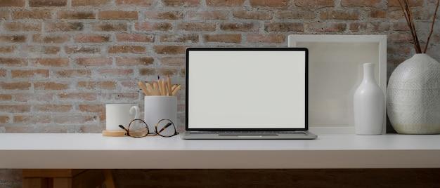 Moderner schreibtisch mit laptop mit weißem bildschirm