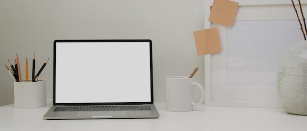 Moderner schreibtisch mit laptop, rahmen, schreibwaren, becher und dekorationen